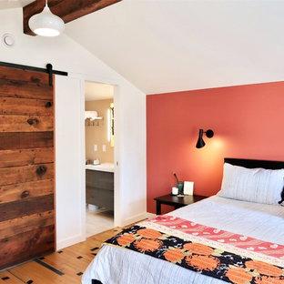 ポートランドの中くらいのエクレクティックスタイルのおしゃれな主寝室 (オレンジの壁、淡色無垢フローリング、コーナー設置型暖炉、マルチカラーの床)
