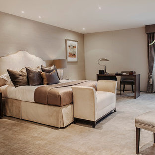 Example of a transitional master carpeted bedroom design in London with beige walls