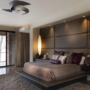 Idee per una grande camera matrimoniale minimal con pareti beige, pavimento in legno massello medio, camino classico e cornice del camino in pietra