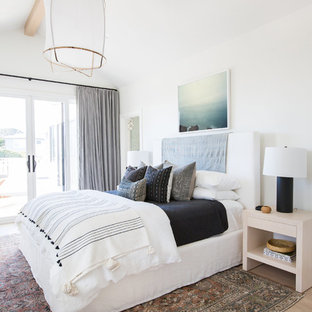 Photo of a coastal bedroom in San Diego with white walls, light hardwood flooring, no fireplace and brown floors.