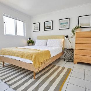 Modelo de dormitorio principal, nórdico, de tamaño medio, con paredes blancas, suelo de baldosas de cerámica y suelo blanco