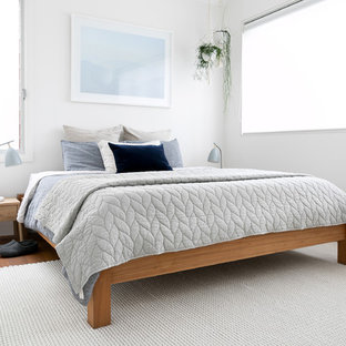 Photo of a contemporary bedroom in Sydney with white walls, medium hardwood floors and brown floor.