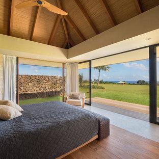 Example of an island style master limestone floor and gray floor bedroom design in Hawaii with beige walls