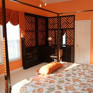 Foto di una camera degli ospiti eclettica di medie dimensioni con pareti arancioni, moquette, pavimento grigio, camino lineare Ribbon e cornice del camino in legno