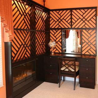 Immagine di una camera degli ospiti eclettica di medie dimensioni con pareti arancioni, moquette, camino lineare Ribbon, cornice del camino in legno e pavimento grigio