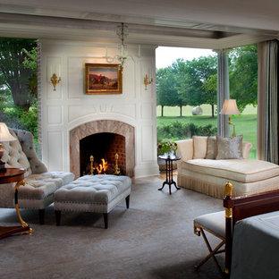 Klassisk inredning av ett stort huvudsovrum, med en standard öppen spis, vita väggar, ljust trägolv, en spiselkrans i trä och beiget golv