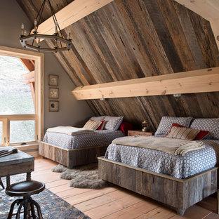 Ejemplo de dormitorio rústico, de tamaño medio, con suelo de madera en tonos medios, paredes grises y suelo marrón