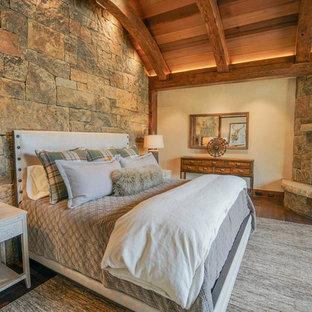 Großes Uriges Hauptschlafzimmer mit beiger Wandfarbe, dunklem Holzboden, Eckkamin, Kaminumrandung aus Stein und braunem Boden in Denver