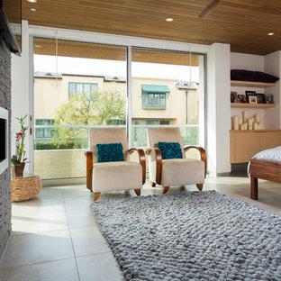 Неиссякаемый источник вдохновения для домашнего уюта: хозяйская спальня среднего размера в стиле модернизм с бежевыми стенами, бетонным полом, горизонтальным камином, фасадом камина из камня и серым полом