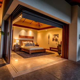 Foto de dormitorio principal, tropical, de tamaño medio, con paredes beige y suelo de piedra caliza