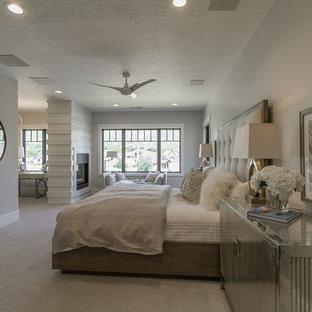 Exemple d'une grand chambre chic avec un mur gris, une cheminée double-face, un manteau de cheminée en bois et un sol beige.