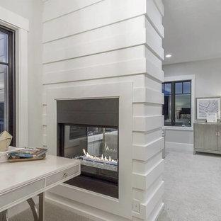 Идея дизайна: большая хозяйская спальня в стиле современная классика с серыми стенами, ковровым покрытием, двусторонним камином, фасадом камина из дерева и бежевым полом