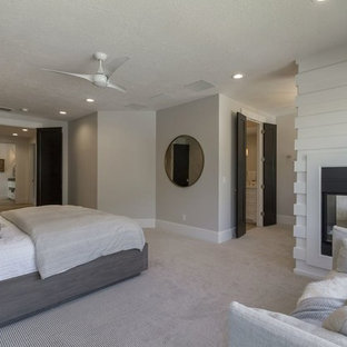 Inspiration for a large transitional master carpeted and beige floor bedroom remodel in Salt Lake City with gray walls, a two-sided fireplace and a wood fireplace surround