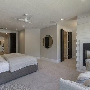 Idéer för ett stort klassiskt huvudsovrum, med grå väggar, heltäckningsmatta, en dubbelsidig öppen spis, en spiselkrans i trä och beiget golv