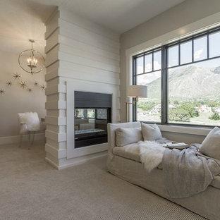 Idées déco pour une grand chambre classique avec un mur gris, une cheminée double-face, un manteau de cheminée en bois et un sol beige.
