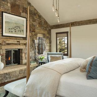 Свежая идея для дизайна: хозяйская спальня в стиле рустика с темным паркетным полом, печью-буржуйкой, фасадом камина из камня и бежевыми стенами - отличное фото интерьера