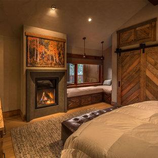 Modelo de dormitorio principal, rural, grande, con paredes beige, suelo de madera clara, chimenea tradicional y marco de chimenea de yeso