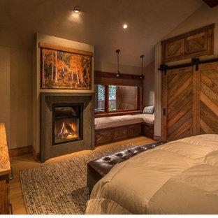 Ejemplo de dormitorio principal, rural, de tamaño medio, con paredes grises, suelo de madera clara, chimenea tradicional y marco de chimenea de hormigón