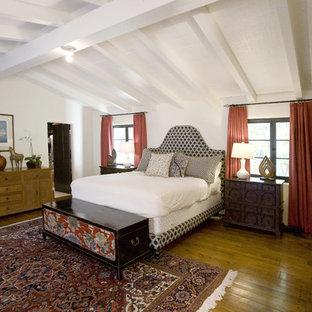 Immagine di una camera da letto minimal con pareti bianche, pavimento in legno massello medio e pavimento giallo