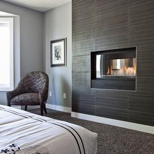 Modelo de habitación de invitados actual, de tamaño medio, con paredes grises, moqueta, chimenea de doble cara y marco de chimenea de baldosas y/o azulejos