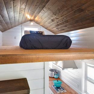 Foto di una piccola camera da letto stile loft costiera con pareti bianche, pavimento in compensato e nessun camino