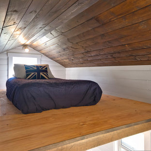 Design ideas for a small beach style loft-style bedroom in Vancouver with white walls, plywood floors and no fireplace.