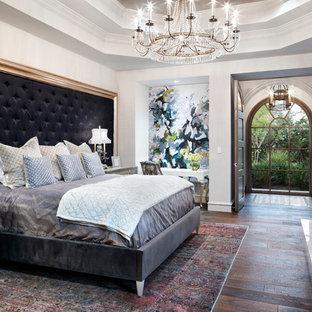 Esempio di una grande camera padronale classica con camino classico, cornice del camino in pietra, pareti bianche, parquet scuro e pavimento marrone