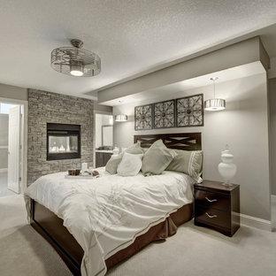Пример оригинального дизайна: хозяйская спальня среднего размера в современном стиле с бежевыми стенами, ковровым покрытием, двусторонним камином и фасадом камина из камня