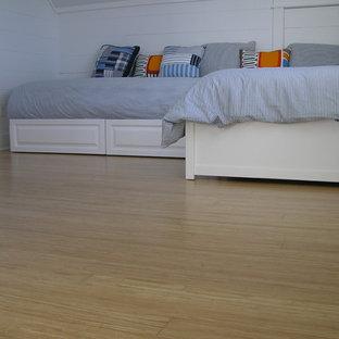 Esempio di una camera da letto design con pavimento in bambù e pavimento giallo