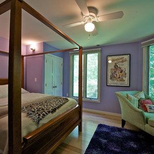 Immagine di una camera degli ospiti minimalista di medie dimensioni con pareti viola, parquet chiaro e nessun camino