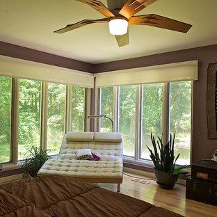 Immagine di una grande camera matrimoniale moderna con pareti viola, parquet chiaro e nessun camino