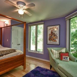 Foto de habitación de invitados moderna, de tamaño medio, sin chimenea, con paredes púrpuras y suelo de madera clara