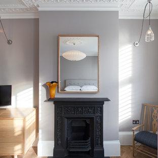 ロンドンの中くらいのコンテンポラリースタイルのおしゃれな主寝室 (グレーの壁、濃色無垢フローリング、標準型暖炉、金属の暖炉まわり、茶色い床)
