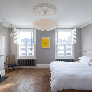 This is an example of a medium sized contemporary master bedroom in London with grey walls and medium hardwood flooring.