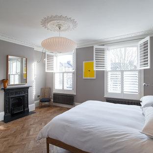 Esempio di una camera matrimoniale contemporanea di medie dimensioni con pareti grigie, pavimento in legno massello medio, camino classico e cornice del camino in metallo