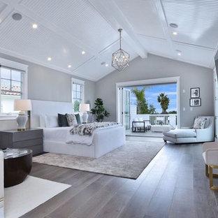 ロサンゼルスの大きいコンテンポラリースタイルのおしゃれな主寝室 (グレーの壁、無垢フローリング、標準型暖炉、金属の暖炉まわり、茶色い床) のインテリア