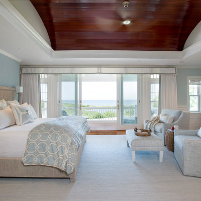 Example of a large beach style master medium tone wood floor and brown floor bedroom design in Boston with blue walls