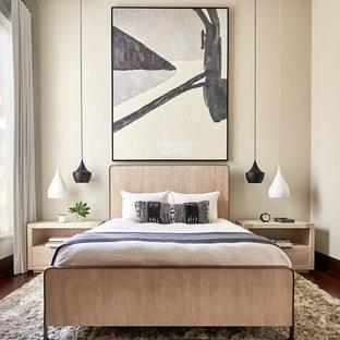 Cette photo montre une chambre parentale tendance de taille moyenne avec un mur beige, un sol en bois foncé, aucune cheminée et un sol marron.