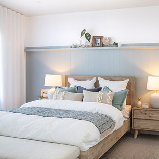 This is an example of a large beach style master bedroom in Sydney with blue walls, carpet, no fireplace and beige floor.