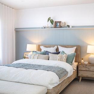 Inspiration pour une grande chambre marine avec un mur bleu, aucune cheminée et un sol beige.