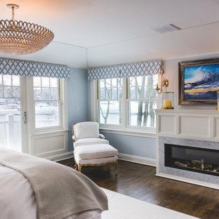 Foto di una grande camera matrimoniale chic con pareti blu, parquet scuro, camino lineare Ribbon e cornice del camino in pietra