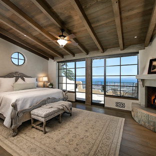 Bedroom - mid-sized mediterranean master dark wood floor and brown floor bedroom idea in Santa Barbara with beige walls, a corner fireplace and a stone fireplace