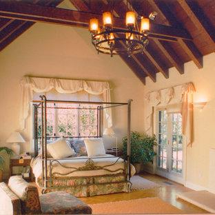 サンフランシスコの大きいトラディショナルスタイルのおしゃれな主寝室 (白い壁、淡色無垢フローリング、標準型暖炉、漆喰の暖炉まわり、茶色い床)