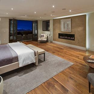 Идея дизайна: большая хозяйская спальня в современном стиле с бежевыми стенами, паркетным полом среднего тона, горизонтальным камином и фасадом камина из штукатурки