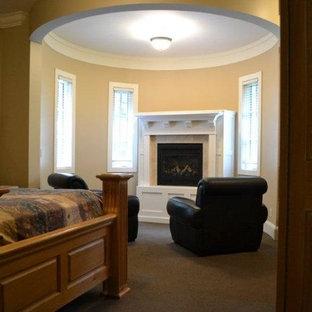Diseño de dormitorio principal, retro, grande, con paredes beige, moqueta, chimenea de esquina y marco de chimenea de madera