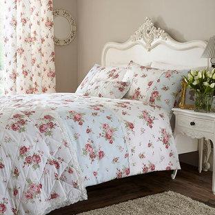 Modelo de dormitorio principal, romántico, de tamaño medio, con paredes beige y suelo de madera en tonos medios
