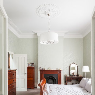 Свежая идея для дизайна: большая хозяйская спальня в классическом стиле с зелеными стенами, ковровым покрытием, стандартным камином и фасадом камина из дерева - отличное фото интерьера