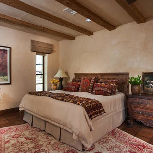 This is an example of a mid-sized master bedroom in Phoenix with beige walls, terra-cotta floors and brown floor.