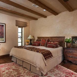 フェニックスの中サイズのサンタフェスタイルのおしゃれな主寝室 (ベージュの壁、テラコッタタイルの床、茶色い床) のレイアウト