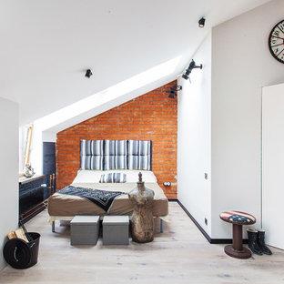 Стильный дизайн: хозяйская спальня в стиле лофт с белыми стенами, светлым паркетным полом и печью-буржуйкой - последний тренд